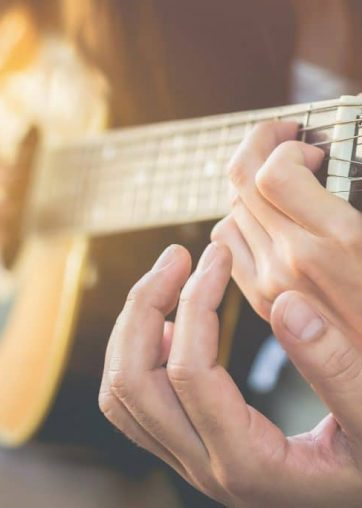 Men's hands are teaching women to play guitar.This image is blurred and Soft focus.
